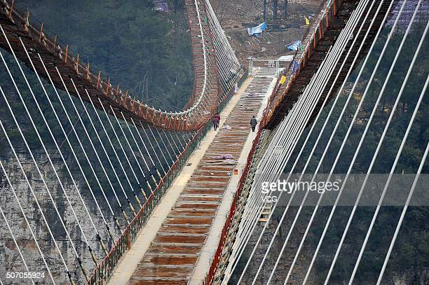 Workers install a piece of glass on a suspension bridge approximately 300 metres above ground at The Grand Canyon of Zhangjiajie on January 27 2016...