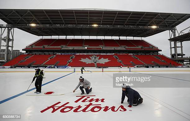 Workers install a 'Tim Hortons' logo during the build out of the outdoor rink for the 2017 Scotiabank NHL Centennial Classic between the Detroit Red...
