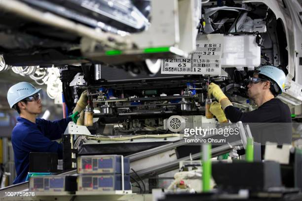 Workers install an engine unit to a Toyota Motor Corp Crown vehicle on the production line of the company's Motomachi factory on July 30, 2018 in...