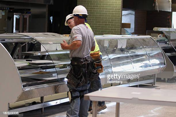 Workers install counters inside a new Whole Foods Market Inc. Store under construction in Park Ridge, Illinois, U.S., on Tuesday, Sept. 17, 2013....