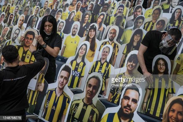 Workers install cut-out portraits of Fenerbahce SK fans at Fenerbahce Sukru Saracoglu Stadium on June 10, 2020 in Istanbul, Turkey. Fenerbahce SK...