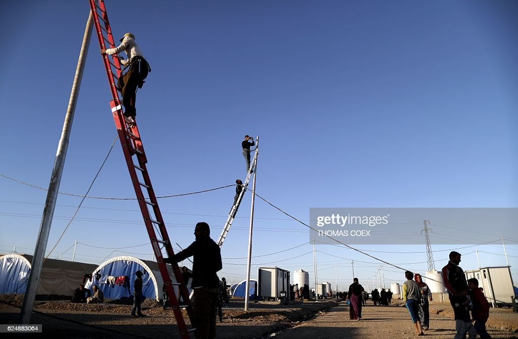 Workers install electric wires for Iraqi refugees as they set up a ...