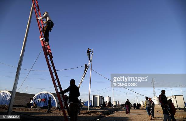 Workers install electric wires for Iraqi refugees as they set up a new part of the Khazir refugee camp near the Kurdish checkpoint of Aski Kalak 40...