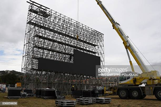 Workers install giant screens in the fanzone site for the UEFA Euro 2016 on the Prado beaches in Marseille where supporters will gather to watch the...
