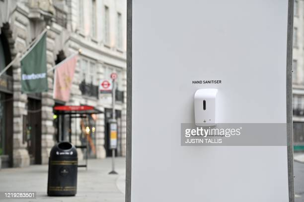 Workers install hand sanitiser stations and signs telling pedestrians and shoppers to adhere to the British government's current social distancing...