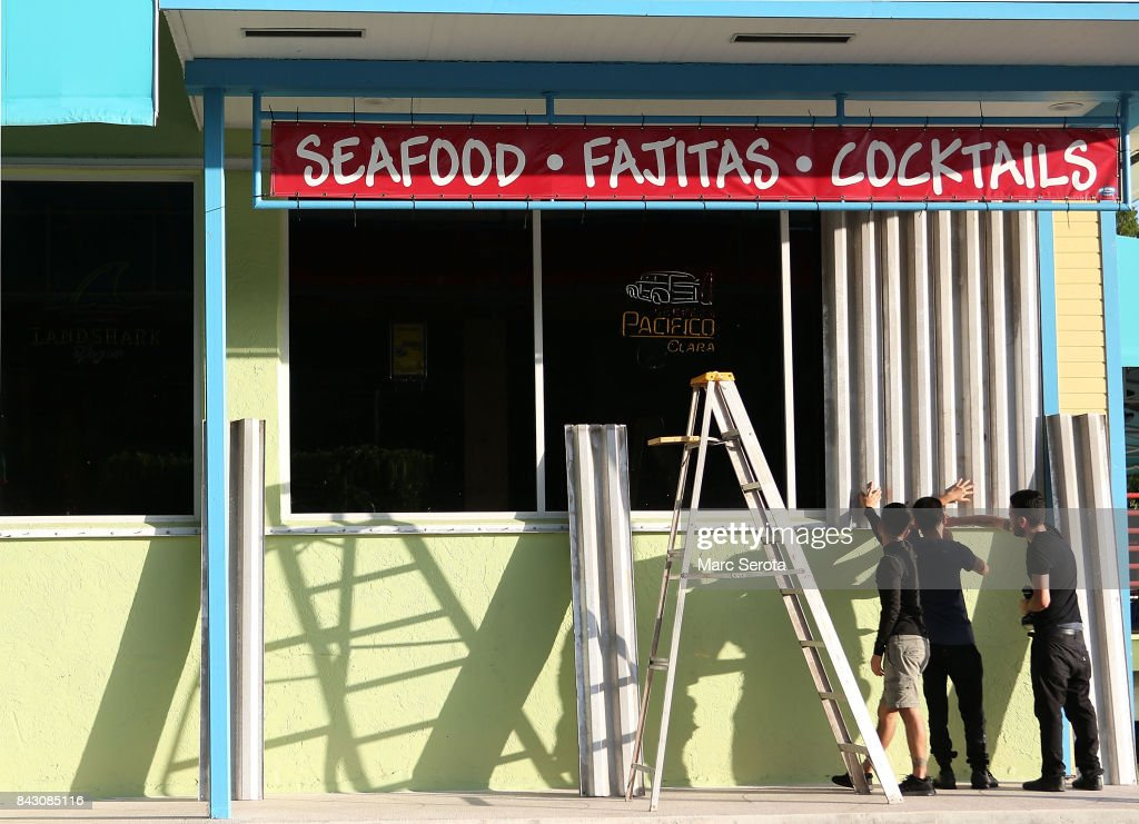 Workers install hurricane shutters on the Puerto Villarta restuarant on Overseas Highway in the Florida Keys on Septeber 5, 2017 in Islamorada, Florida. Residents are evacuating ahead of Hurricane Irma, a powerful storm expected to make landfall this weekend.