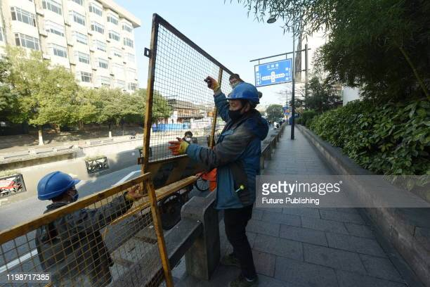 Workers install iron fences on roads outside an old neighborhood to prevent the spread of new coronavirus pneumonia, Hangzhou City, Zhejiang...