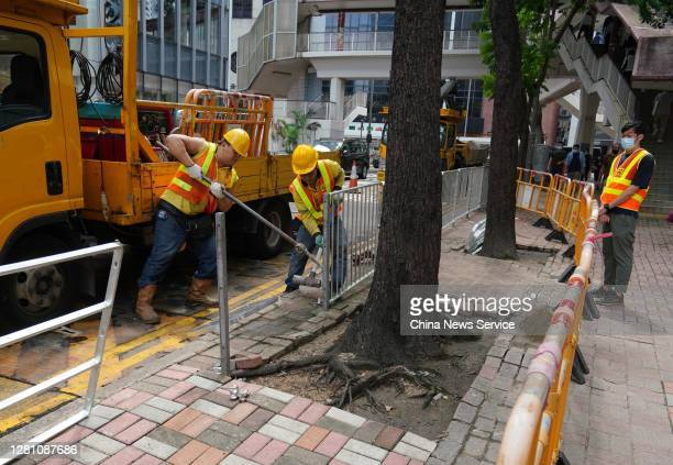 Workers install iron railing in front of Hong Kong Police Headquarters on October 19, 2020 in Hong Kong, China.