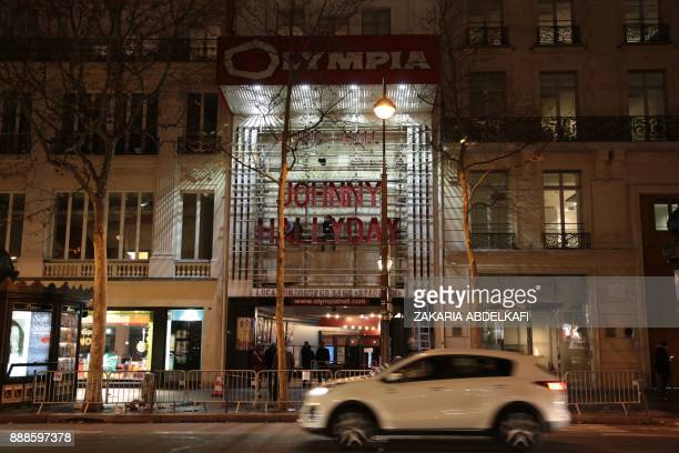 Workers install lights on the Olympia Music theater with the name of Johnny Hallyday in Paris on December 8 2017 France will hold a national funeral...