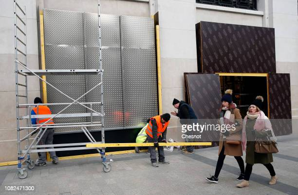 Workers install metal panels to protect the facade of the Monoprix supermarket against possible damage on the eve of a demonstration of 'Yellow...