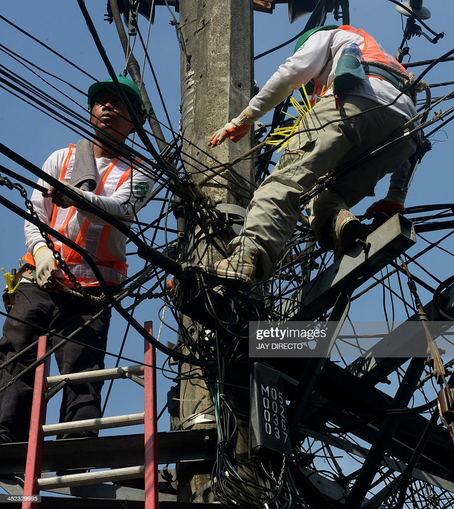 Workers install new fiber optics cables for a telephone company in Manila on February 28, 2013. The Philippines economy is expected to grow about seven percent in 2013, as expansion in October-December is stunted by this month's devastating typhoon, the government said on November 28. AFP PHOTO / Jay DIRECTO