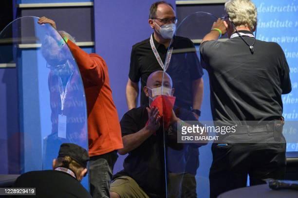 Workers install plexiglass protections between the debaters on the stage of the debate hall ahead of the vice presidential debate in Kingsbury Hall...