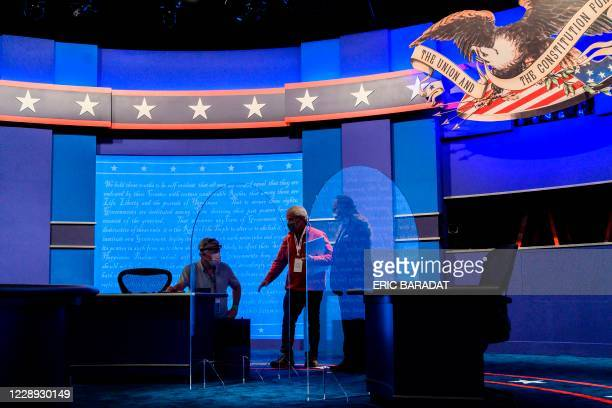 Workers install plexiglass protections on the stage of the debate hall ahead of the vice presidential debate in Kingsbury Hall of the University of...