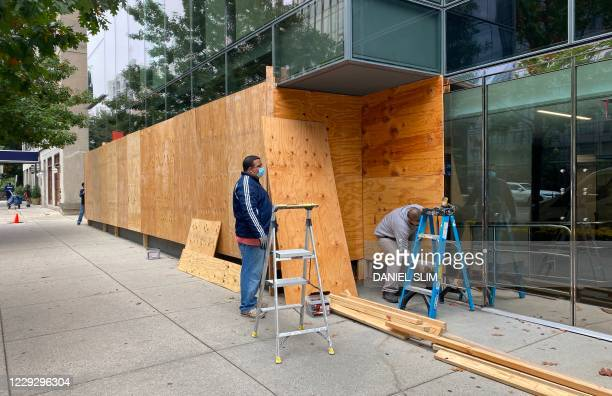 Workers install protections on building facades near the White House as building managers and local businesses fear violent demonstrations ahead of...