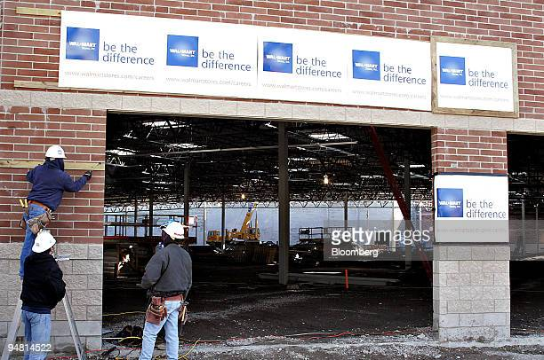 Workers install signs outside a WalMart store under construction in Chicago Illinois Tuesday April 4 2006 WalMart Stores Inc will add 50 stores in...