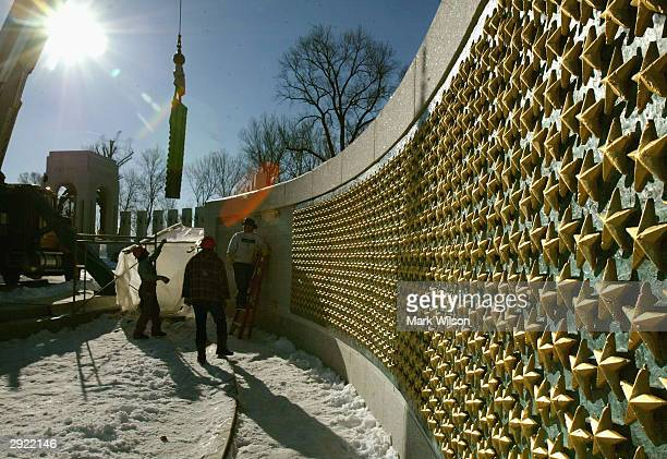 Workers install the commemorative centerpiece of the National World War II Memorial February 2 2004 in Washington DC The centerpiece consists of a...
