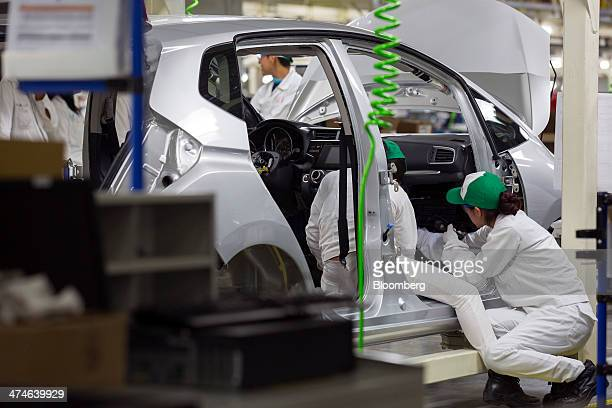 Workers install the control panel on a Honda Fit vehicle on the production line after the opening ceremony for Honda Motor Co's new plant in Celaya...