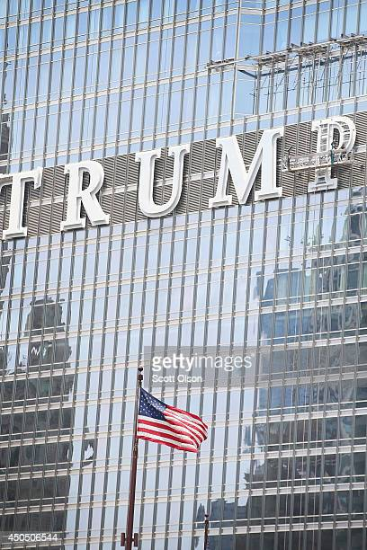 Workers install the final letter for a giant TRUMP sign on the outside of the Trump Tower on June 12, 2014 in Chicago, Illinois. Many in the city are...