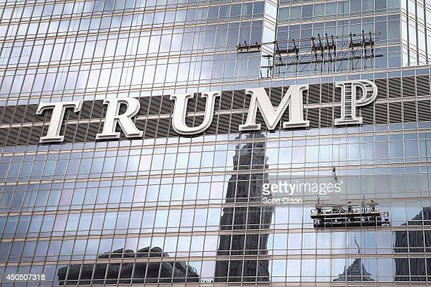 Workers install the final letter for a giant TRUMP sign on the outside of the Trump Tower on June 12 2014 in Chicago Illinois Many in the city are...