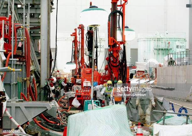 Workers install underground pipes to create frozen soil walls on the south side of the No. 4 reactor building at the Fukushima Daiichi nuclear power...