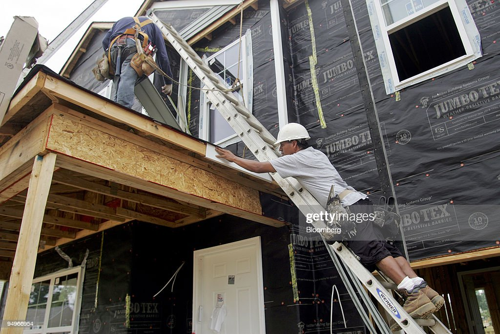 Workers install vinyl siding on a Centex home under