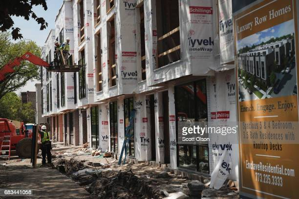 Workers install windows in a townhome complex under construction on May 15, 2017 in Chicago, Illinois. The National Association of Home Builders said...
