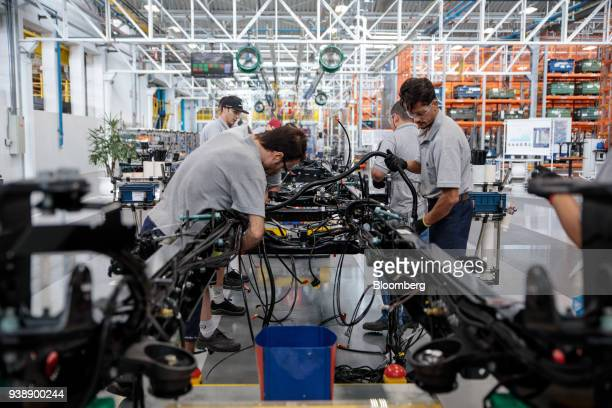 Workers install wiring while assembling Daimler AG MercedesBenz trucks on the new production line at the company's factory in Sao Bernardo do Campo...