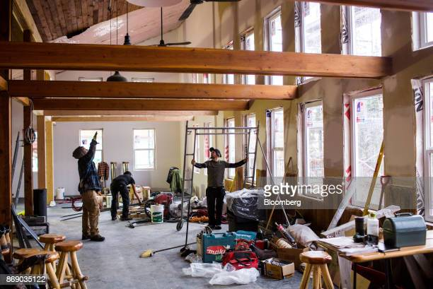 Workers install wood beams inside a lodge under construction at the Red Mountain ski resort in Rossland British Columbia Canada on Thursday Oct 19...