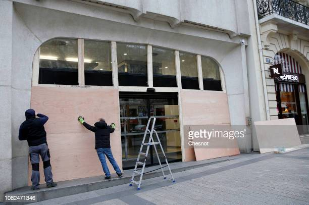 Workers install wood panels to protect a shop gainst possible damage on the eve of a demonstration of 'Yellow vests' on the ChampsElysees Avenue near...