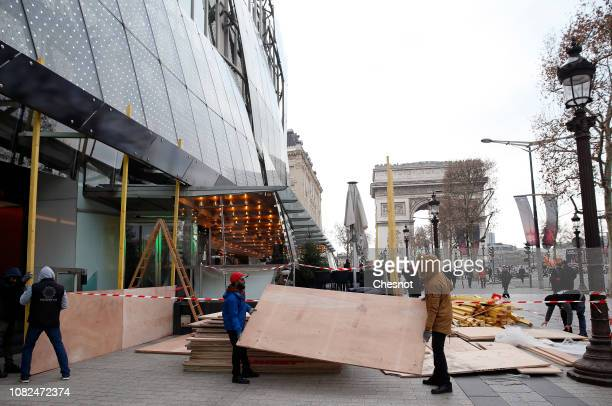 Workers install wood panels to protect the Drugtore Publicis against possible damage on the eve of a demonstration of 'Yellow vests' on the...