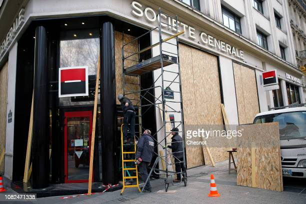Workers install wood panels to protect the facade of the Societe Generale bank against possible damage on the eve of a demonstration of 'Yellow...