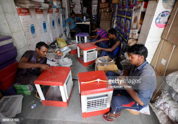 Workers installing air cooler in a shop at Kamla Market as temperature rises on April 17 2017 in New Delhi India Delhi residents continued to bear...