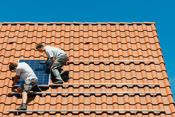 workers installing solar panel on roof framework of new home picture