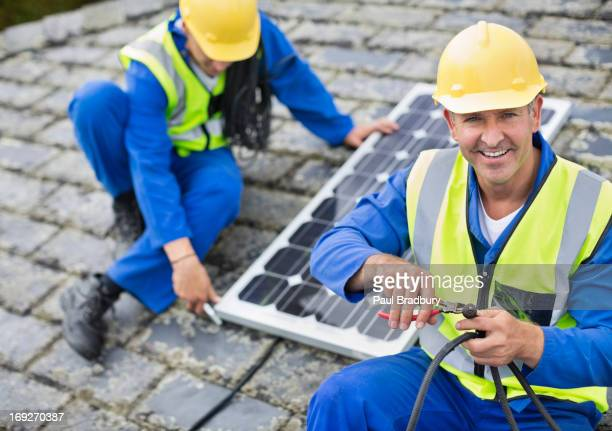 Arbeiter installieren Sonnenkollektor auf dem Dach