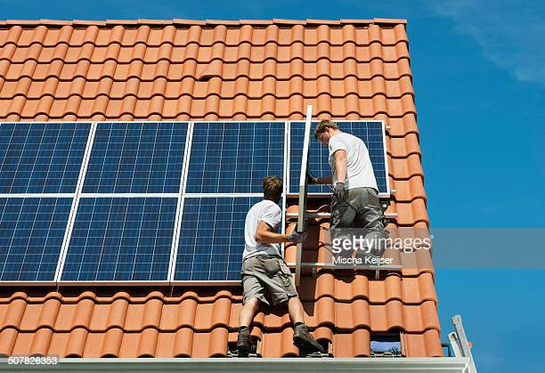 workers installing solar panels on roof framework of new home, netherlands - new zealand stockfoto's en -beelden