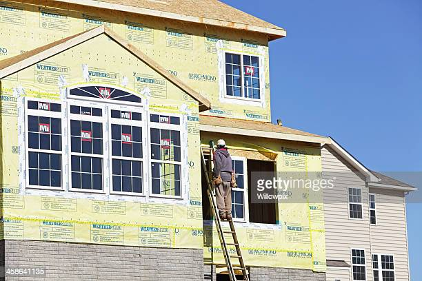 Workers Installing Windows on New Construction Home
