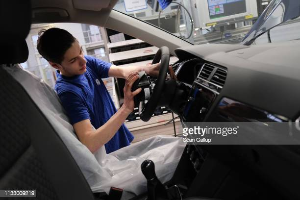 A workers installs an airbag into the steering wheel of a car on the assembly line for Volkswagen Touareg Touran and TRoc models at the Volkswagen...