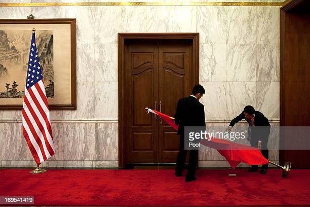 Workers iron a Chinese national flag while a US national flag is placed in front of a Chinese traditional painting before a meeting of the US...