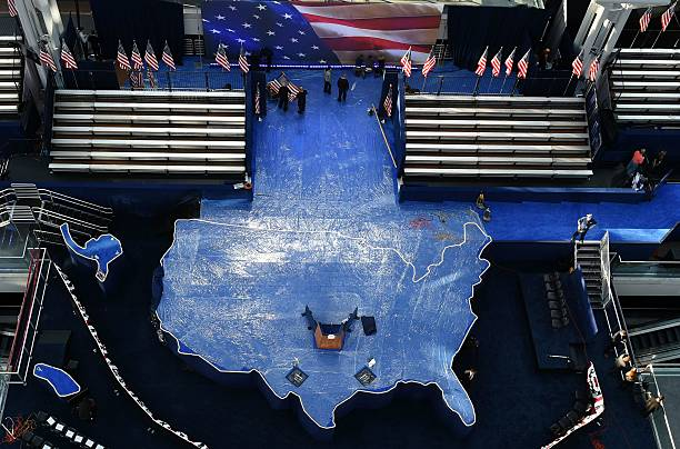 Workers iron a US flag as they prepare the US map shaped stage for ...