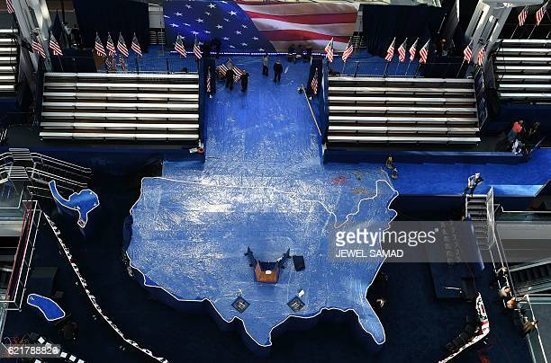 Workers iron a US flag as they prepare the US map shaped stage for Democratic presidential candidate Hillary Clinton's election night event at the...