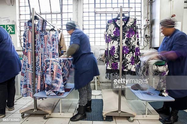 workers ironing dress in garment factory - top garment stock-fotos und bilder