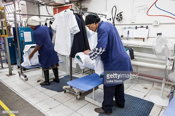 workers ironing shirt in garment factory - top garment stock-fotos und bilder