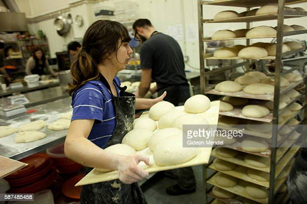 Workers knead and make the popular organic sourdough Hackney Wild bread loaf at the E5 Bakehouse This is a new East London artisan bakery and coffe...