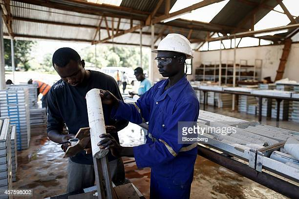 Workers label rock core samples used to select drilling locations at the Kibali gold mine operated by Randgold Resources Ltd in Kibali Democratic...
