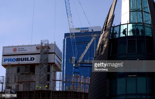 Workers labor at a construction site as people are silhouetted at the observation desk of the Bell Tower right in the Elizabeth Quay area of Perth...