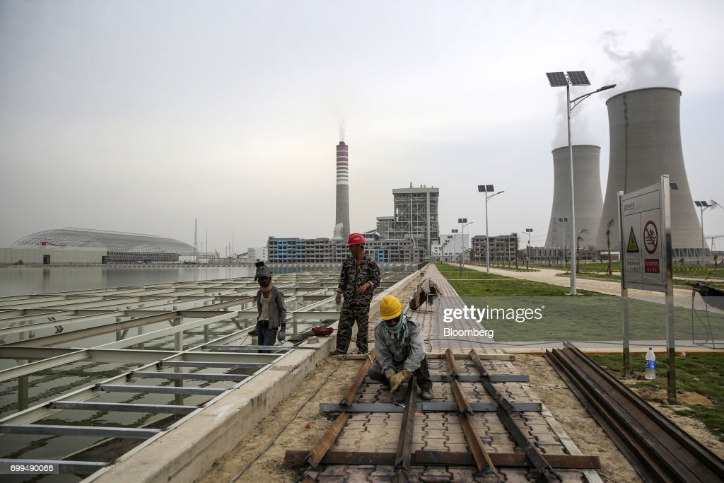Workers labor at a construction site at the Sahiwal coal power plant owned by China`s stateowned Huaneng Shandong Rui Group in Sahiwal Punjab...