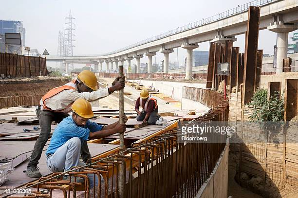 Workers labor at a construction site below an elevated track operated by Rapid MetroRail Gurgaon Ltd near DLF Cybercity in Gurgaon India on Wednesday...
