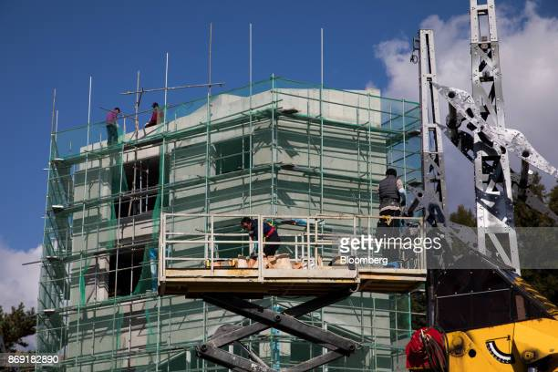 Workers labor at a construction site in Hoenggyeri village area of Pyeongchang Gangwon South Korea on Friday Oct 20 2017 With less than 100 days to...