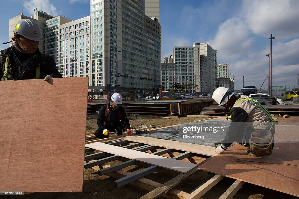 Workers labor at a construction site in Sejong, South Korea, on Tuesday, Dec. 4, 2012. The construction of Sejong City 120 kilometers (75 miles) south of the capital fulfills the vision of the late President Roh Moo Hyun, who pledged to reduce the dominance of Seoul and pump money into a region courted for its swing voters. Photographer: SeongJoon Cho/Bloomberg via Getty Images