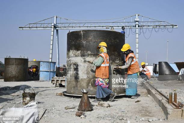 Workers labor at an under construction sewerage system on the project site for a 920squarekilometer industrial area located on the DelhiMumbai...